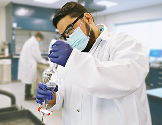 Technician wearing protective gear conducting cGMP analytical testing in pharmaceutical manufacturing lab