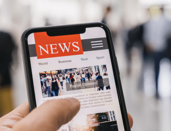 Hand holding smartphone with list of News articles